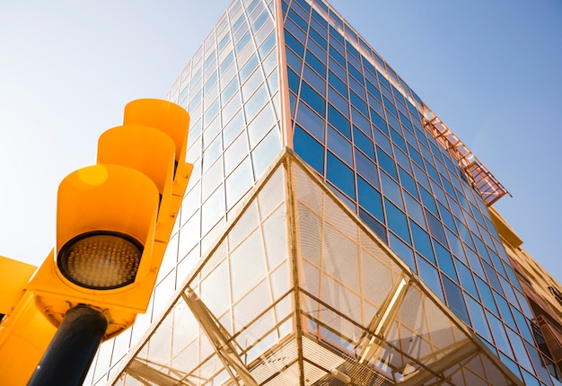 Взгляд низкого угла светофора около современного корпоративного здания против голубого неба