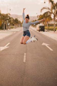 興奮した若い女性ジェスチャーピースサインを身に着けているローラースケートジャンプ