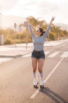 ローラースケートを着て笑顔の女性スケーターが道路上で平和のジェスチャーを作る