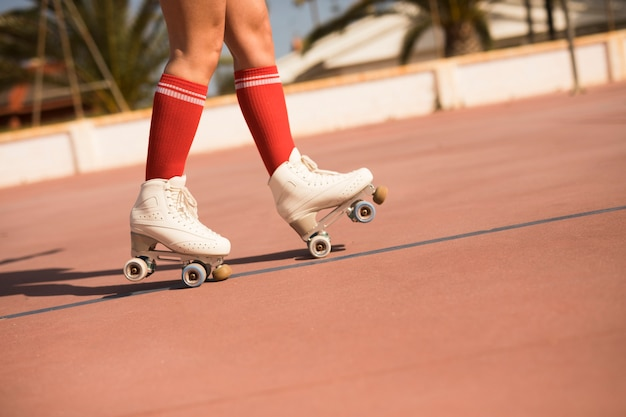 Низкая часть женщины кататься на коньках на открытом корте