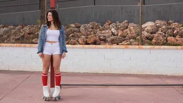 よそ見ポールの前に立っている笑顔の若い女性スケーター
