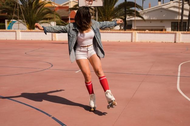 屋外コートでスケートをする若い女性