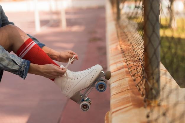 Крупным планом фигуристка, опираясь ногой на забор, связывая кружева