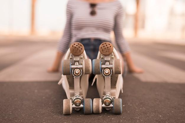 彼女の足にローラースケートで地面に座っているピンぼけの若い女性