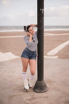 鉄の柱の近くに立っている笑顔の女性スケーターの肖像画