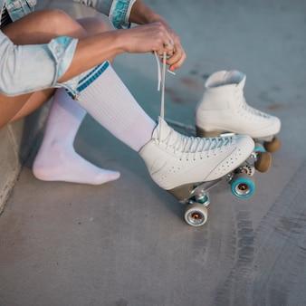 Молодая фигуристка завязывает шнурок на роликах