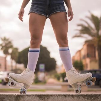 ベンチでバランスの取れている女性スケーターの低いセクション
