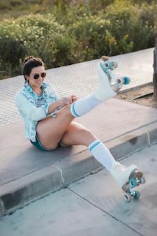 ローラースケートレースを引っ張って笑顔のファッショナブルな若い女性