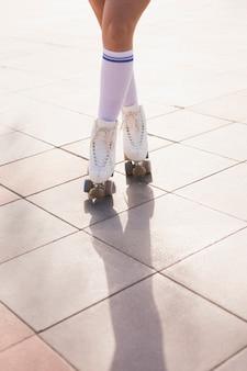 Низкая часть женщины в роликовых коньках, стоя со скрещенными ногами на полу