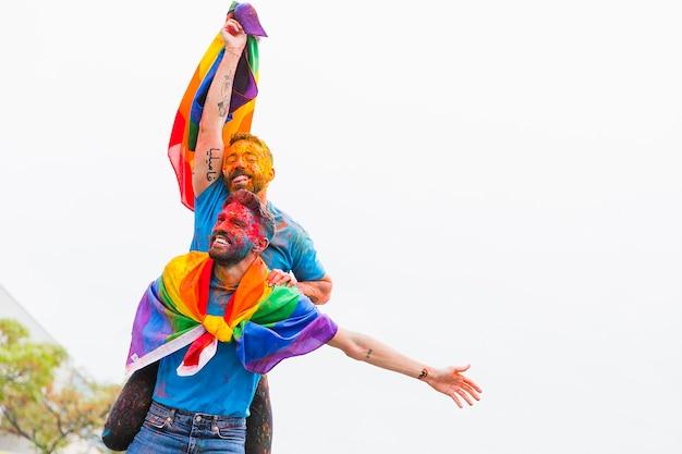 フェスティバルで歓喜の塗られた面を持つ同性愛カップル