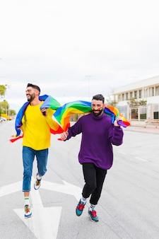 Гей-пара бежит по дороге с флагами лгбт за спиной