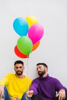 Молодые геи сидят с разноцветными шариками