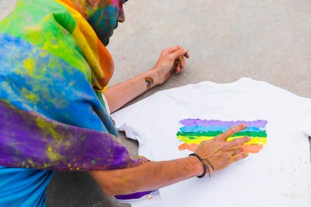 同性愛者の図面の虹色の旗を手で