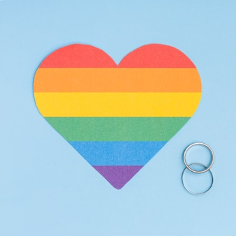 Радужное лгбт-сердце и обручальные кольца на синем фоне