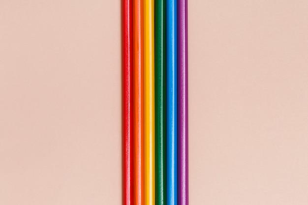 ベージュ色の背景に色とりどりの虹スティック