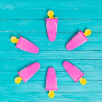 ターコイズブルーのテーブルの上の黄色の箸にアイスキャンデー明るいピンク