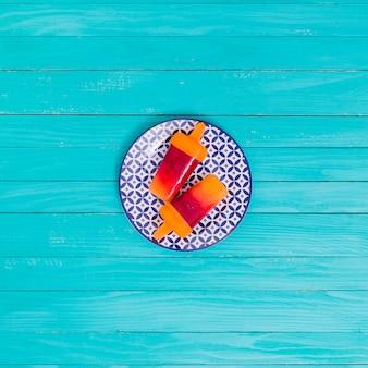 木の表面に皿の上の明るいフルーツアイスキャンデー