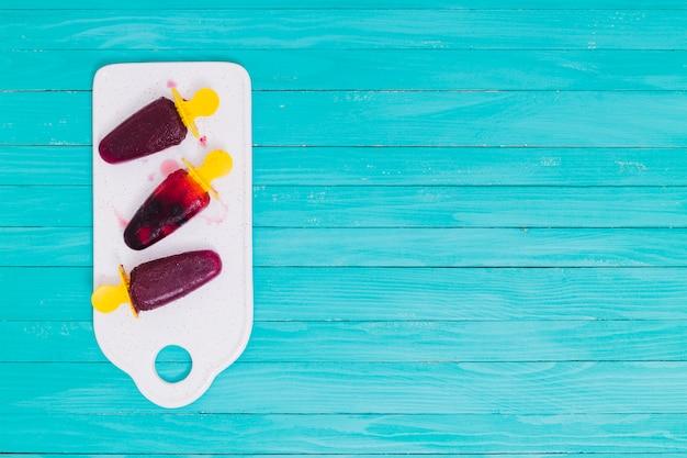 木の表面に白いまな板の上の果実のアイスキャンディー