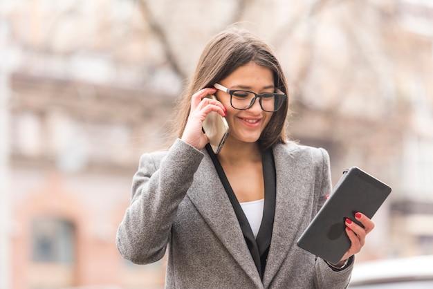 彼女のスマートフォンを使用してブルネットの実業家