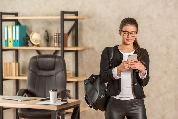 Брюнетка бизнесвумен, используя ее смартфон