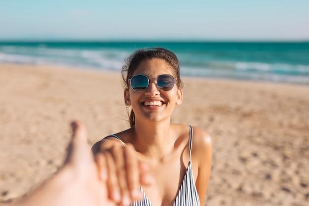 手を握ってビーチで笑顔の女性