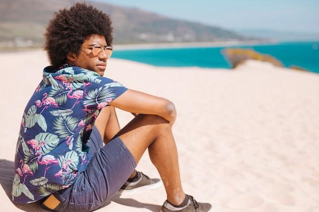 Афро-американский мужчина отдыхает на берегу моря