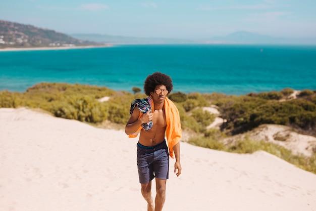 Красивый молодой человек идет вдоль берега моря