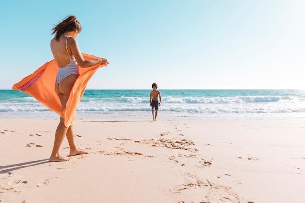 海辺で休んでいる多文化カップル