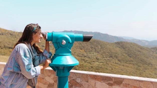 Улыбается женщина, глядя через подзорная труба