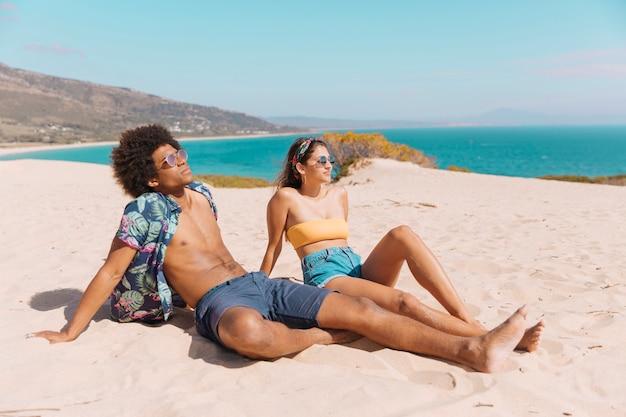 多民族のカップルがビーチで日光浴