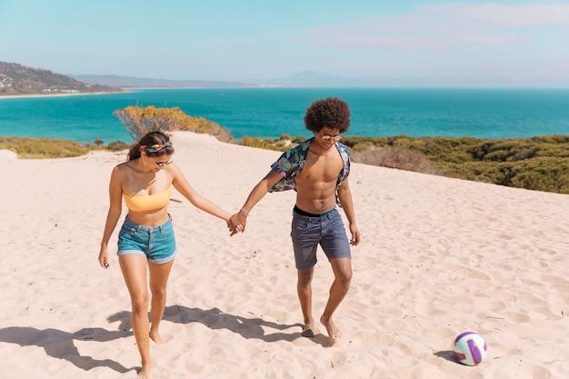 カップルはビーチの上を歩くと手を繋いでいます。
