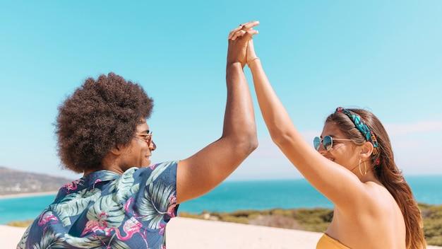手を繋いでいるとビーチで笑顔のカップル