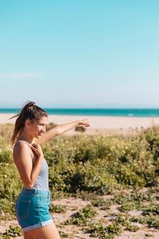 海岸に立っていると前方に手を示す女性