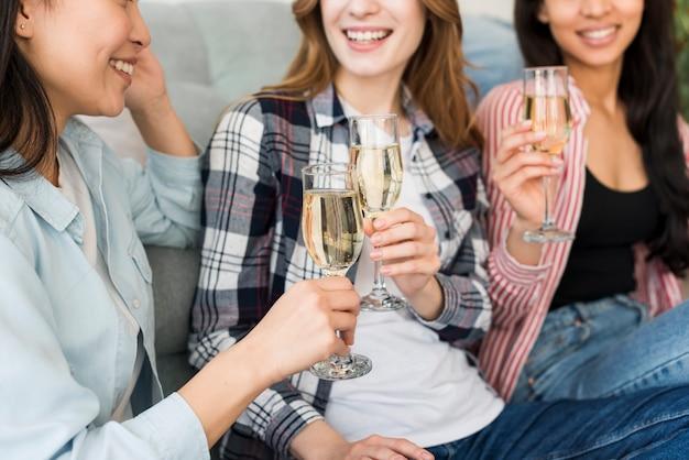 Улыбающиеся и сидящие на диване женщины пьют шампанское