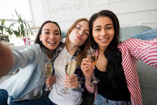 Девушки держат бокалы с напитками и принимают селфи