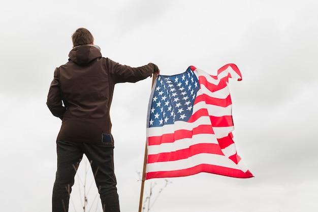 Мужчина стоит возле американского флага