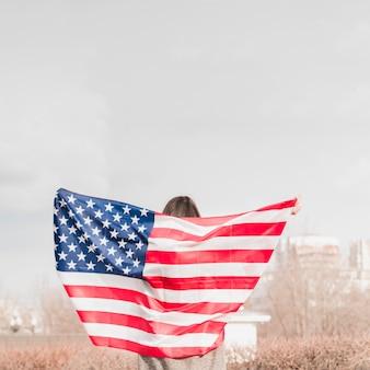 アメリカの国旗と一緒に歩いている女性