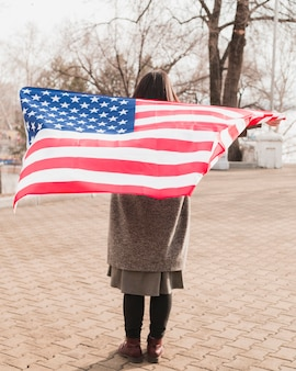 公園でアメリカの国旗を持つ愛国心が強い女性
