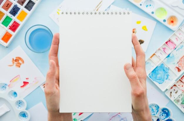 Руки взгляд сверху держа тетрадь в окружении элементов картины