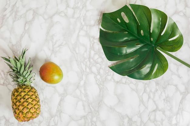 トップビューパイナップル、マンゴー、熱帯の葉