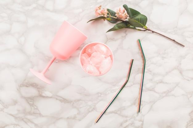 Чашка сверху, цветок и солома на мраморе