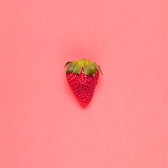 ピンクの背景にジューシーな赤いイチゴ