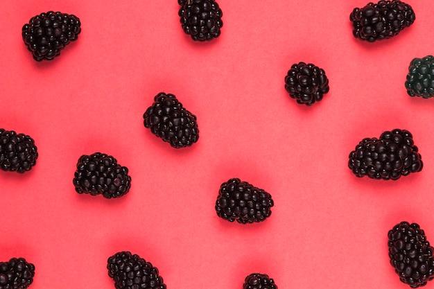 ピンクの背景に熟した甘いブラックベリー