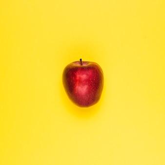 Спелое сочное красное яблоко на желтой поверхности
