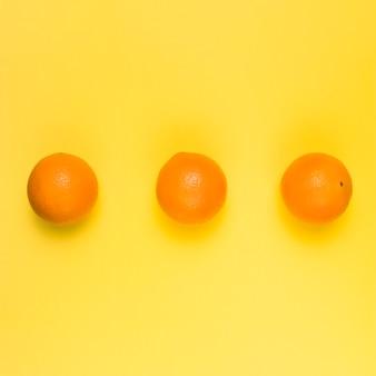 Яркие спелые апельсины на желтом фоне