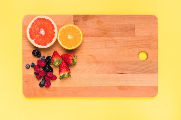 まな板の上のジューシーオレンジレモンストロベリーブラックベリーラズベリーとスグリのスライス