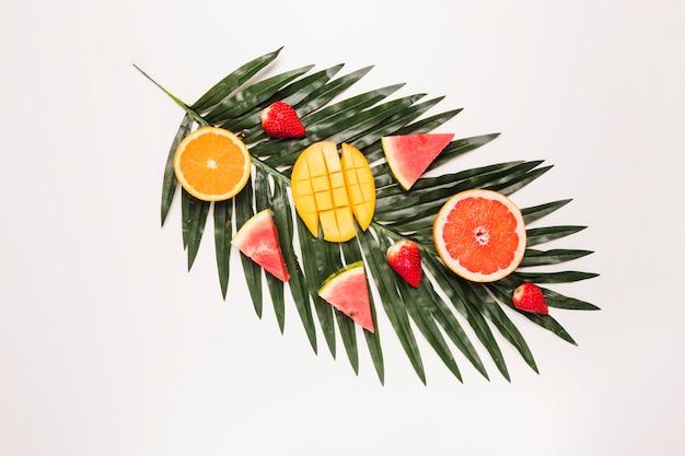 ヤシの葉で食欲をそそる赤いスイカイチゴオレンジマンゴーのスライス