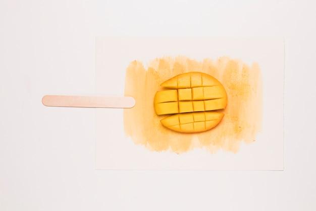 アイスクリームの形で水彩のスプラッシュにさいの目に切ったマンゴー
