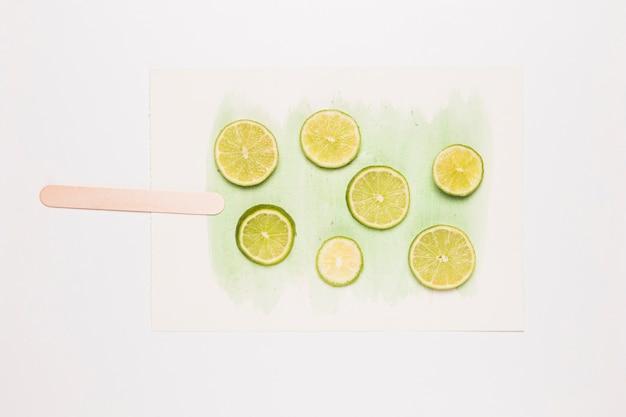 水彩のスプラッシュにアイスクリームの形でライムをカットします。