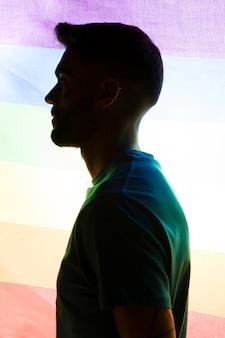 虹色の旗の背景に男